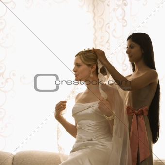 Bridesmaid placing veil.
