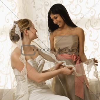 Bridesmaid holding bride's veil.