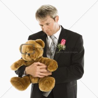 Groom holding teddy bear.