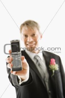 Groom holding cellphone.