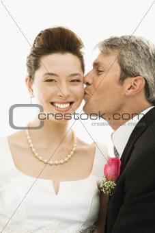 Groom kissing bride.