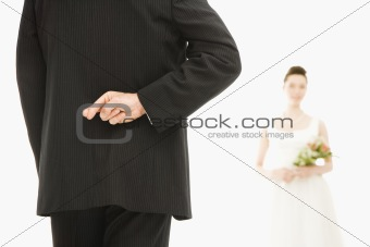 Groom with crossed fingers.