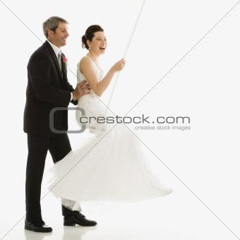 Groom pushing bride in swing.