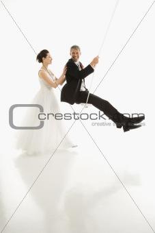Bride pushing groom in swing.
