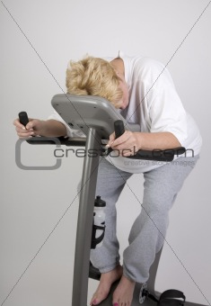 tired woman on exercise bike
