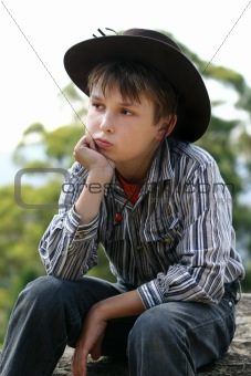 Country cowboy sitting on a rock