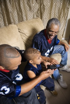 African-American family watching tv with boy holding remote.