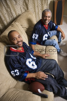 African-American father and son sitting on couch.