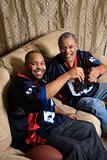 African-American father and son toasting bottles on couch.