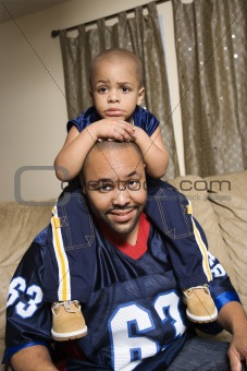 African-American boy sitting on dad's shoulders.