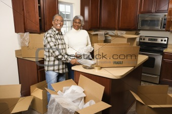 Middle-aged couple unpacking boxes.