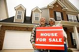 Middle-aged couple holding a for sale sign.