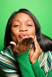 African-American woman wearing green scarf blowing kiss at viewe