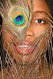 African-American woman looking through peacock feather.