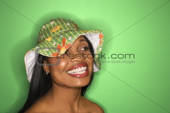 African-American woman wearing green hat on green background.