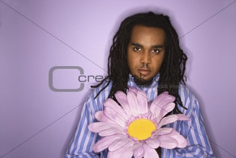 African-American man holding big fake flower.