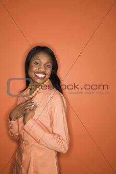 African-American woman wearing orange clothing.