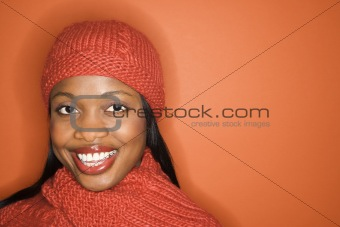 African-American woman wearing orange scarf and hat.