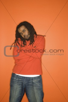African-American man with crossed arms wearing orange clothing.