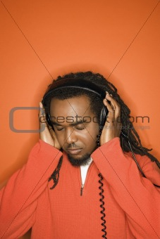 African-American man listening to headphones.