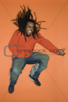African-American man jumping and playing air guitar.