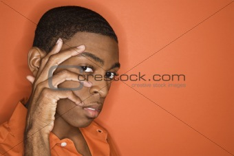African-American man with his hand on his face.
