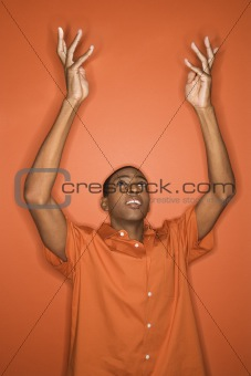 African-American man throwing his arms up in the air.