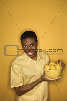 African-American man holding bowl of lemons.