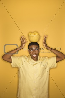 African-American man balancing bowl of lemons on his head.