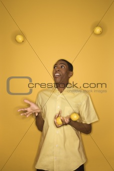 African-American man juggling lemons.