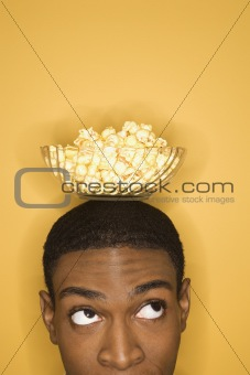 African-American man balancing bowl of popcorn on head.