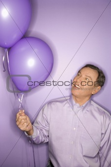 Caucasian man holding purple balloons.