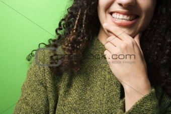 Caucasian woman with hand on chin wearing green clothing.