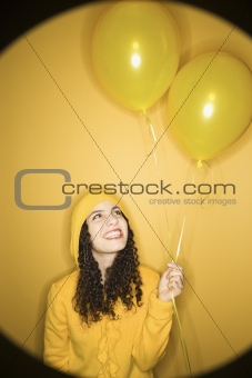 Caucasian woman with balloons wearing yellow raincoat.