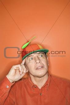Caucasian man wearing propeller cap.