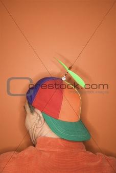 Back view of man wearing propeller cap.