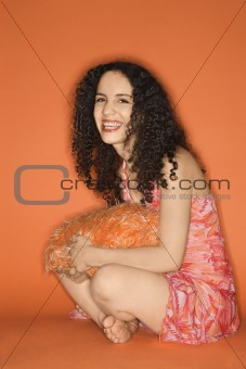 Caucasian woman sitting on floor with pillow.