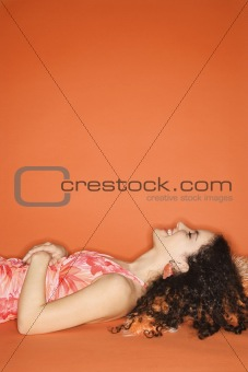 Caucasian woman lying on floor with pillow.