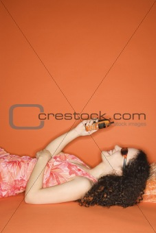 Caucasian woman lying on floor looking at cellphone.