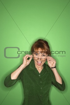 Caucasian woman putting on eyeglasses.