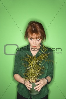 Caucasian woman looking at plant.