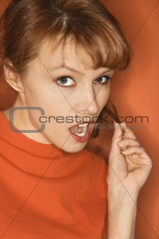 Caucasian woman on orange background.