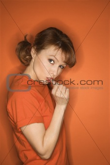 Caucasian woman gesturing with thumb.