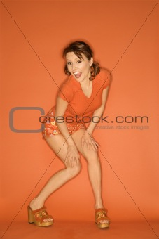 Caucasian woman posing on orange background.