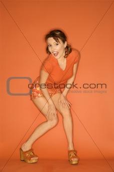 Caucasian woman posing on orange background.
