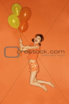 Caucasian woman being lifted into air by balloons.