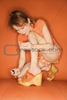 Caucasian woman painting her toenails.