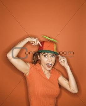 Caucasian woman wearing propeller cap.