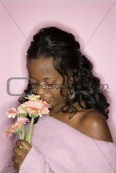 African-American woman smelling flowers.