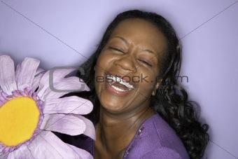 Adult woman holding big purple fake flower.